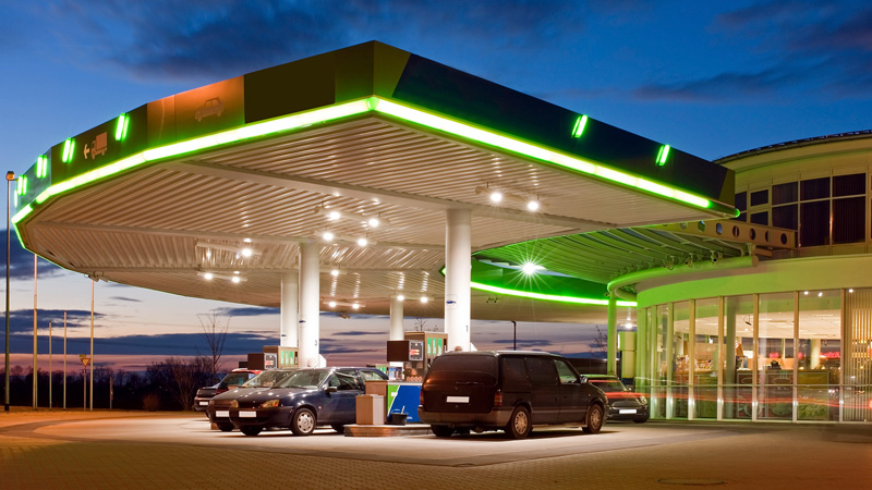 Gas station with all lights on and vehicles at gas pumps.