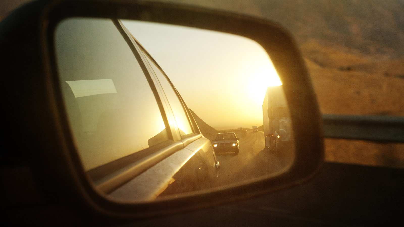 Side mirror on car showing traffic behind car.