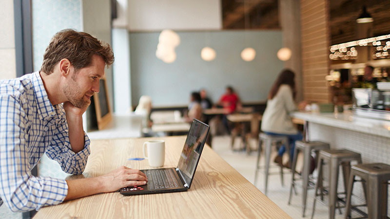 Man in a café looking at his laptop with cup of coffee and credit card next to him