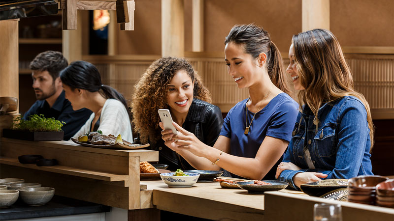 Three friends sitting in a restaurant looking at a smartphone together