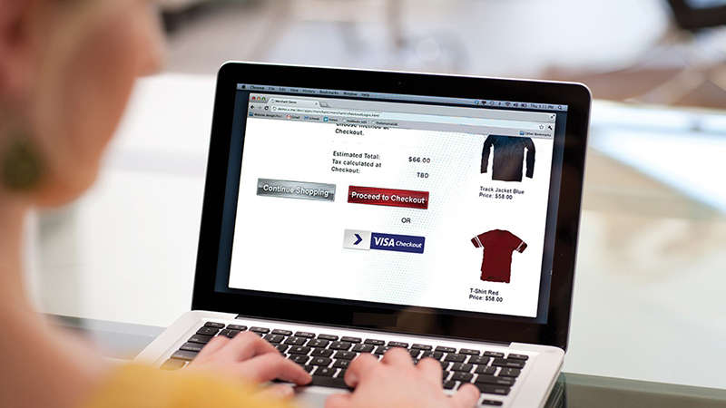 A woman with a laptop doing some online shopping on a website that has Visa Checkout.