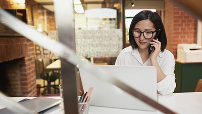 Portrait of young Asian businesswoman speaking by phone while working in modern office, copy space